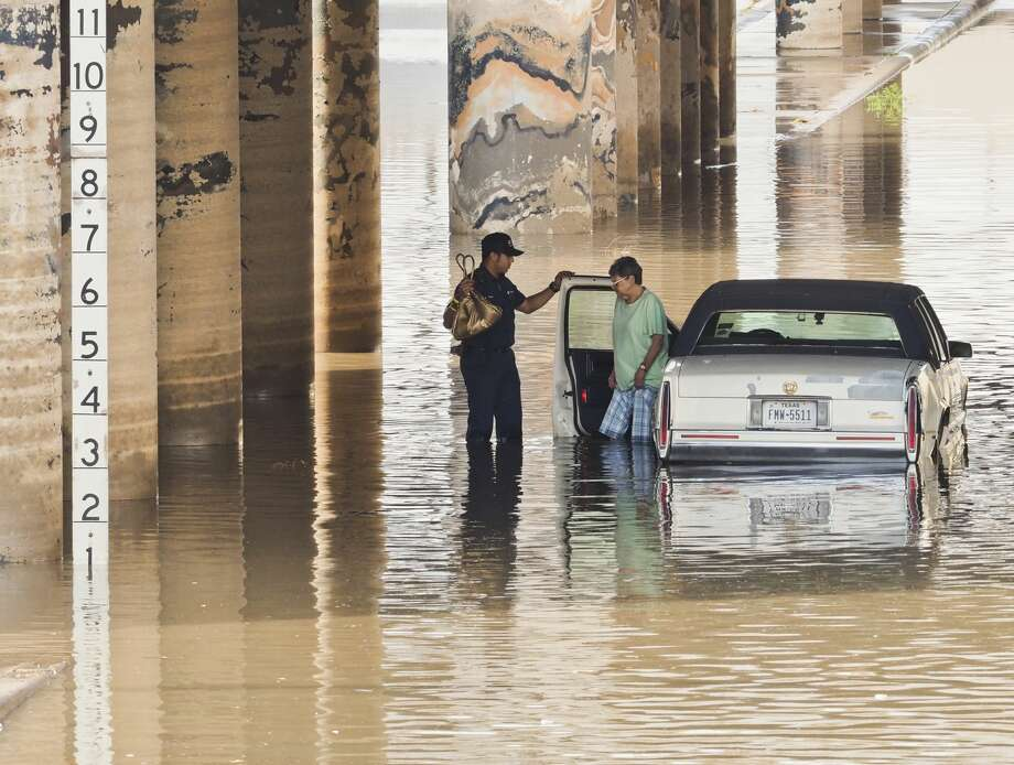 Midland fire department help a driver out of her car after it stalled in water pooled under the train overpass on Big Spring and Front Street 06/04/18 morning. Barricades were in place blocking the roadway, but someone had moved the barricades to allow cars to pass through. Tim Fischer/Reporter-Telegram Photo: Tim Fischer/Midland Reporter-Telegram