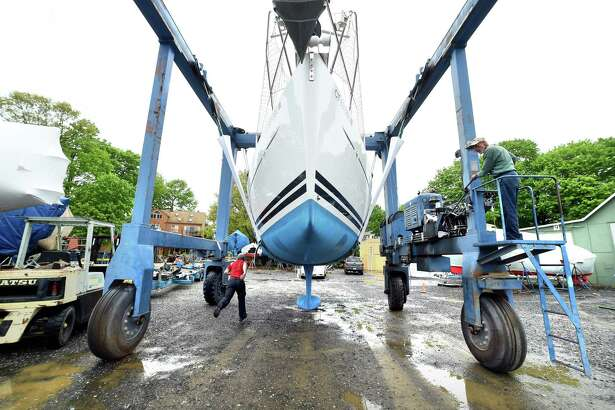 A sailboat is transported to the water after winter storage at the Dutch Wharf Boatyard in Branford on May 17, 2018.