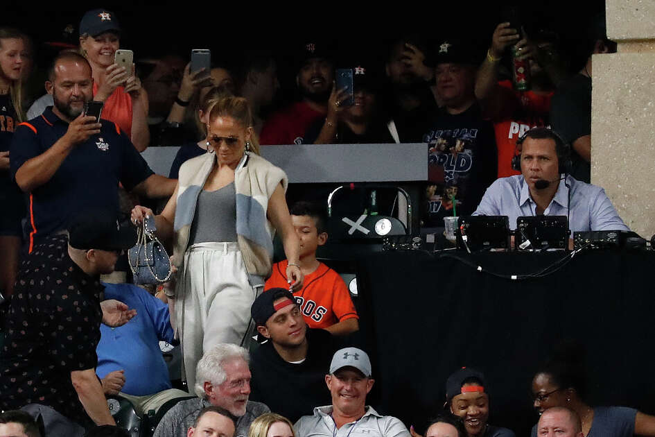 Jennifer Lopez walks past Alex Rodriguez who is at the ESPN booth during the seventh inning of an MLB baseball game at Minute Maid Park, Sunday June 3, 2018, in Houston.