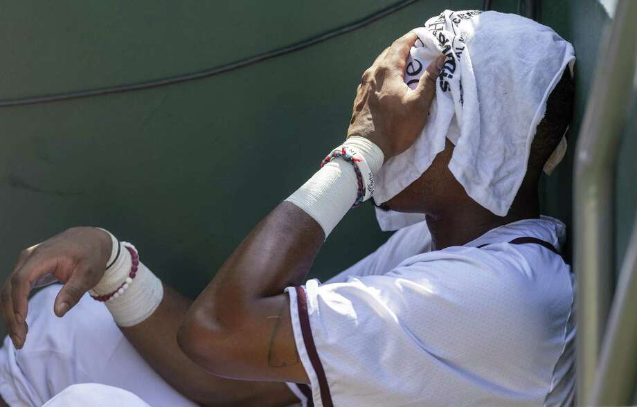 Texas A&M's Allonte Wingate finds shade with a wet towel over his face as temperatures reached 100 degrees during the Aggies' elimination game loss to Indiana on Sunday. Photo: Photos By Stephen Spillman / For The Express-News / stephenspillman@me.com Stephen Spillman