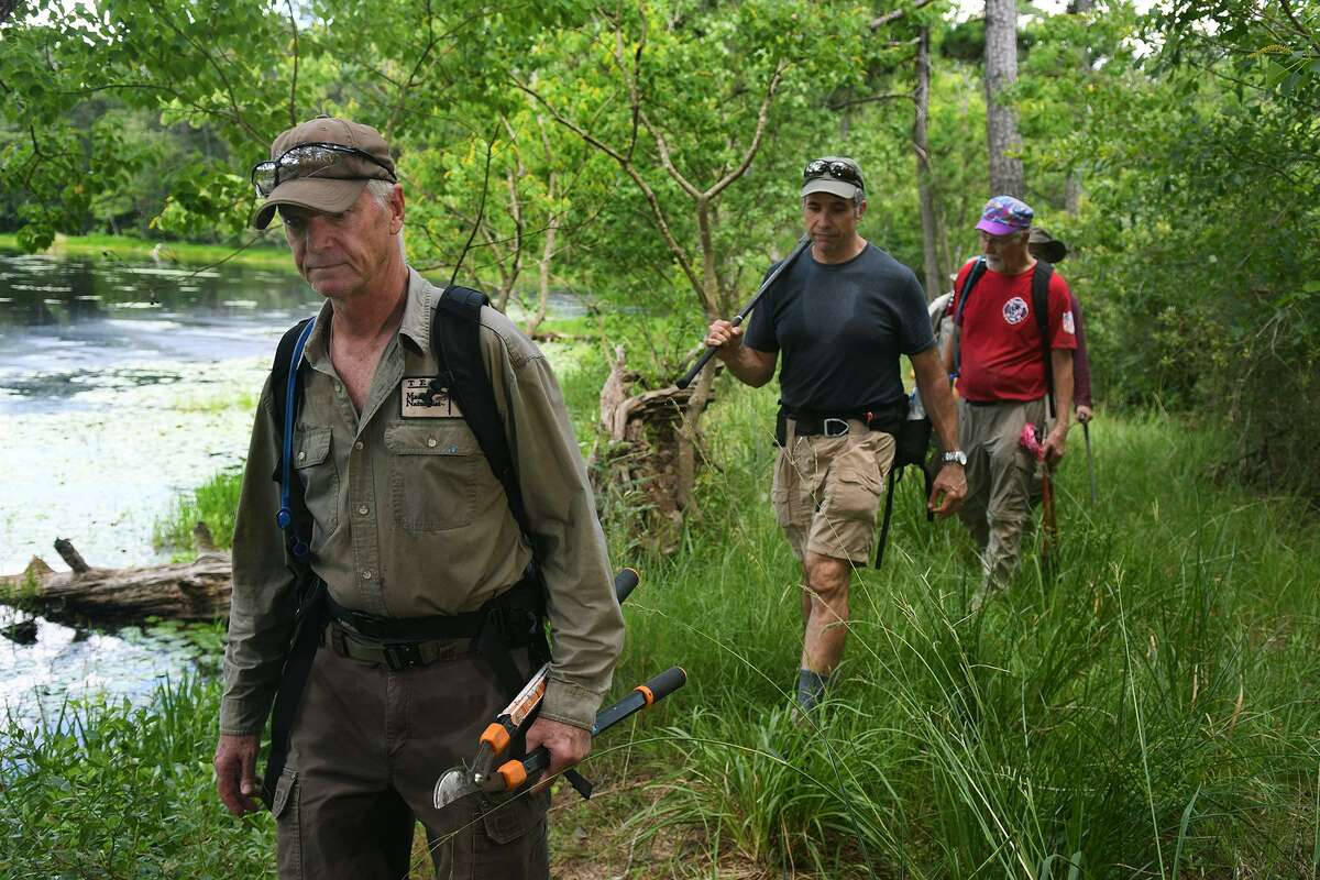 John Stacy, from left, of Houston and a Master Naturalist, leads his fellow volunteers, including Aram Derewetzky, of The Woodlands, and Dean Kahney, of Spring, around a pond as they walk a trail segment during a clearing effort for Bayou Land Conservancy near the Spring Creek Bridge, of The Woodlands, on May 30, 2018. (Jerry Baker/For the Chronicle)