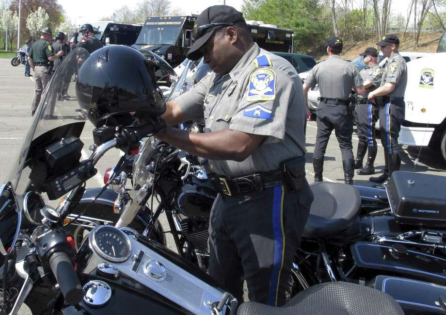 Connecticut Trooper Walter Greene straps his helmet onto his motorcycle in Windsor, Connecticut, in May 2015. Photo: Dave Collins / Associated Press / AP