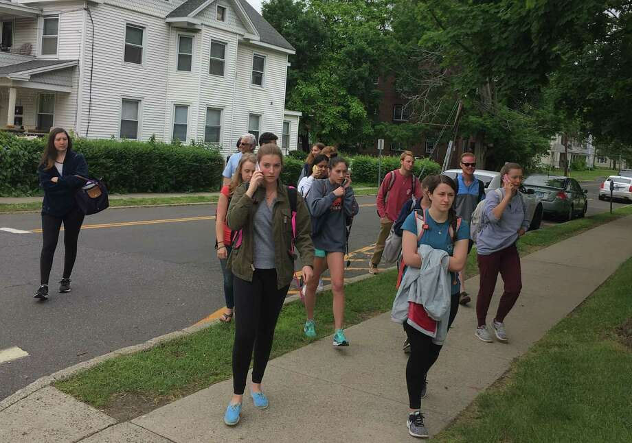 Students were evacuated from White Hall at Western Connecticut State University after a report that a man with a rifle had entered the building. Among those evacuated was Ariana Gravinese, in middle on her cell phone, one of several students in a summer calculus class. The reported rifle turned out to be a microphone stand. Photo: / Dirk Perrefort