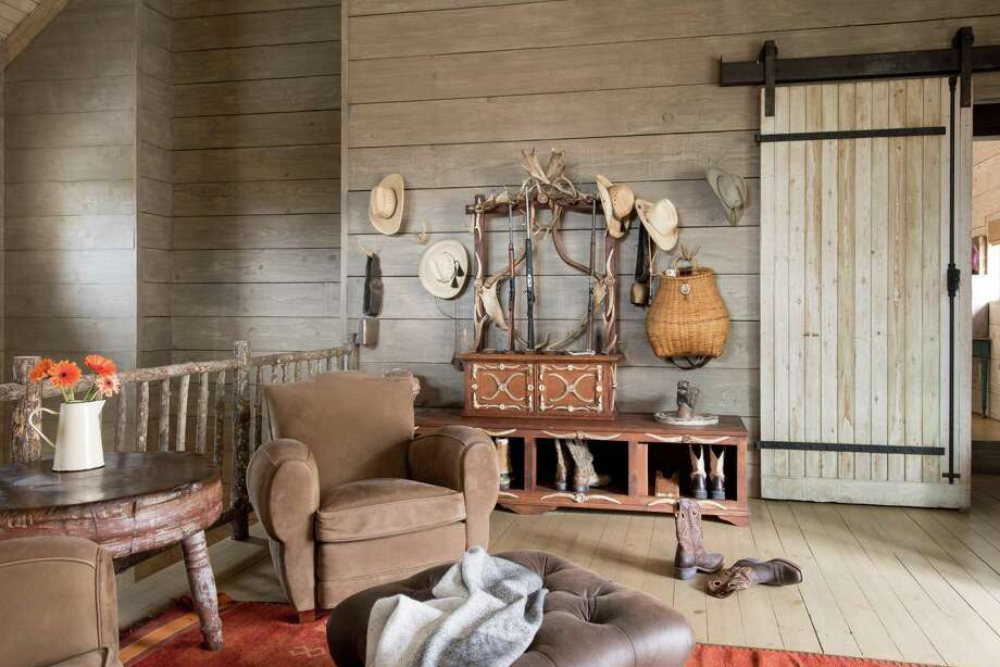 Rustic luxury defines the mud room at this Fredericksburg ranch. A custom rack adorned with deer antlers found on the property holds hats, a decorative bench holds boots and shoes, and an antique basket hanging on the wall holds umbrellas and other gear. Photo: Michael Hunter