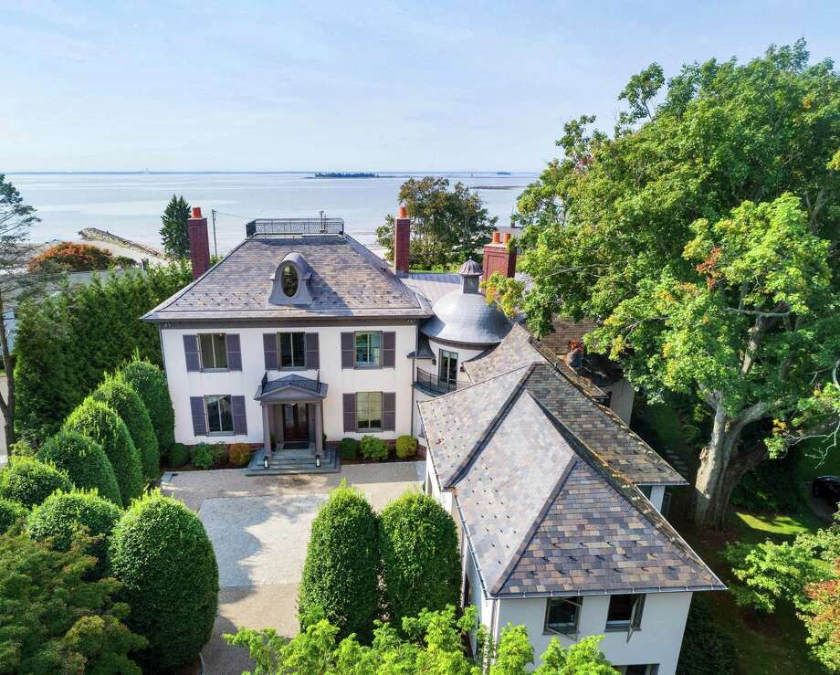 The pale gray stucco colonial house at 6 Bluewater Lane has nearly 12,000 square feet of living space in a waterfront community. / Copyright, Barry A. Hyman, 2017