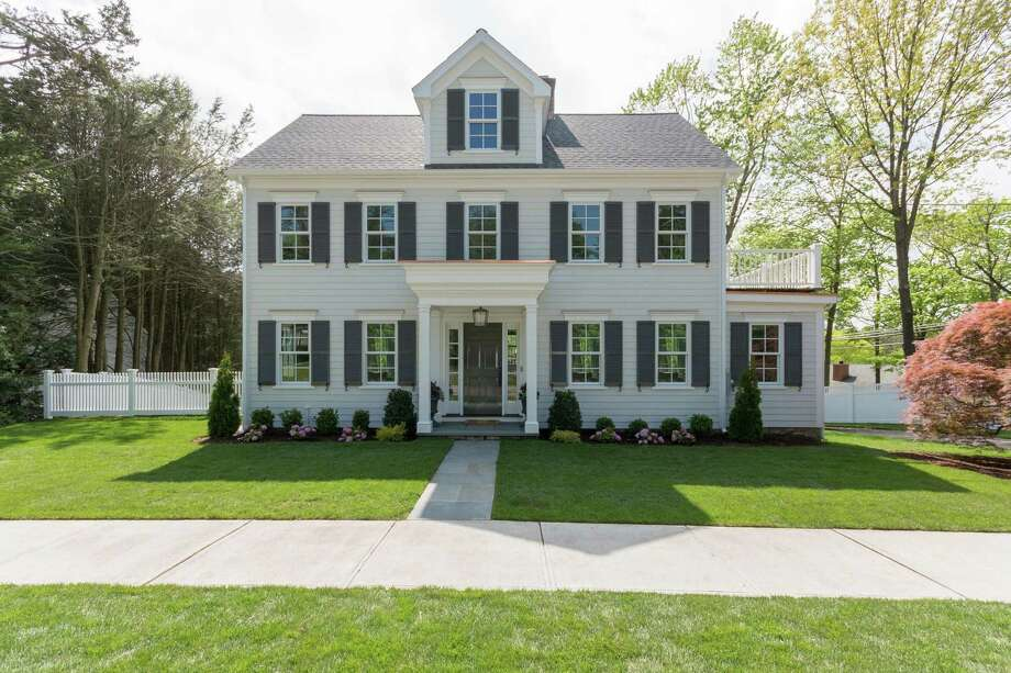 The white clapboard colonial house with gray shutters at 7 Brinckerhoff Avenue is the first project in New Canaan for acclaimed architectural and design firm Coffinier Ku Design.