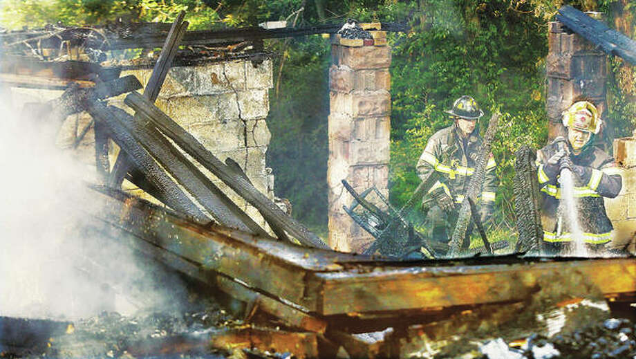 Alton Battalion Chief Dave Eichen, right, hoses down hot spots in the rubble of a house at 3227 Edsall St. in Alton Monday morning as an investigation into the cause of the fire in the vacant house gets underway. The roof of the house collapsed, sending what was left of the structure into the basement shortly after firefighters arrived around 4:30 a.m.