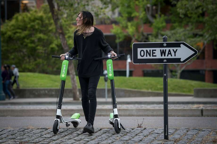 Livia Looper pushes LimeBike scooters in San Francisco, California, U.S., on Tuesday, May 15, 2018. Lime recently introduced the scooters to South Lake Tahoe, to mixed reviews. Photo: David Paul Morris / Bloomberg