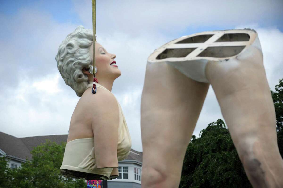 The head and torso of Marilyn Monroe gets lifted off a flatbed truck during the assembly of the 26-foot Marilyn Monroe statue in Latham Park in downtown Stamford, Conn. on Monday, June 4, 2018. The 3,000 pound statue named
