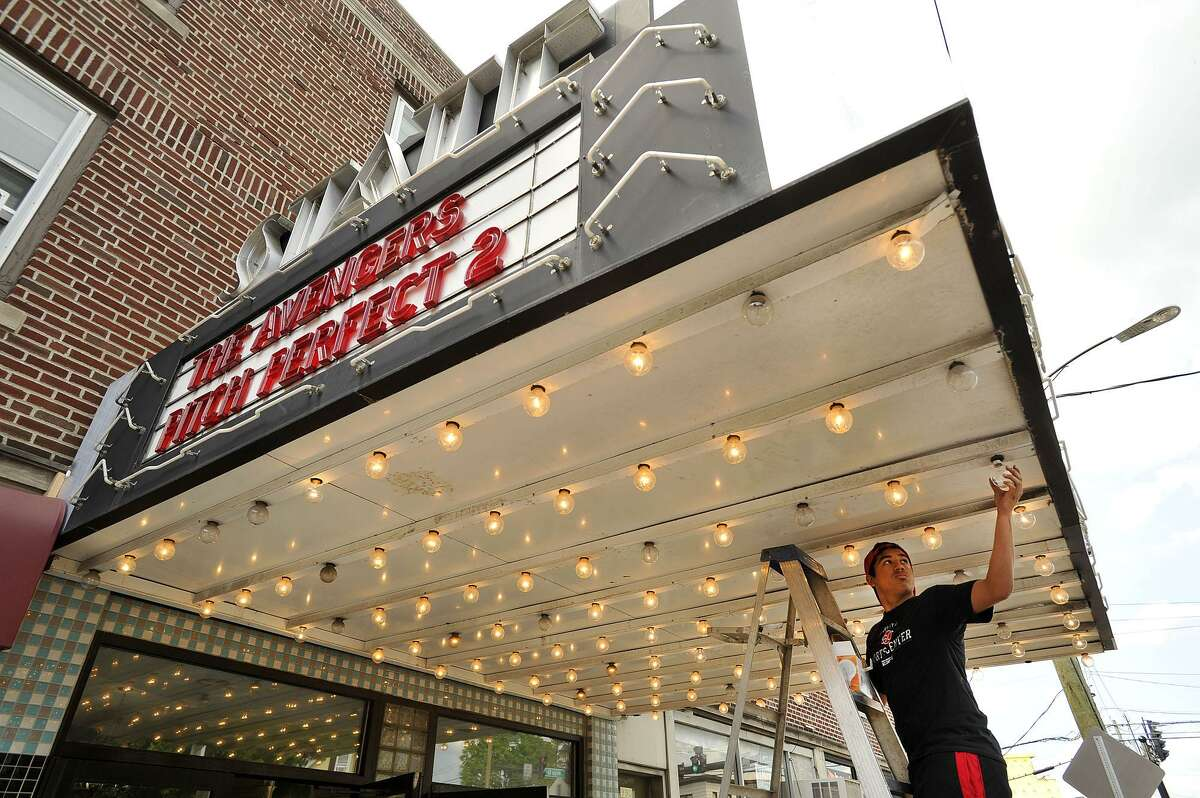 FILE - Concession and maintenance worker Jonathan DaSilva replaces bulbs in the awning of the State Cinema in the Springdale neighborhood of Stamford, Conn., on Sunday, May 17, 2015.