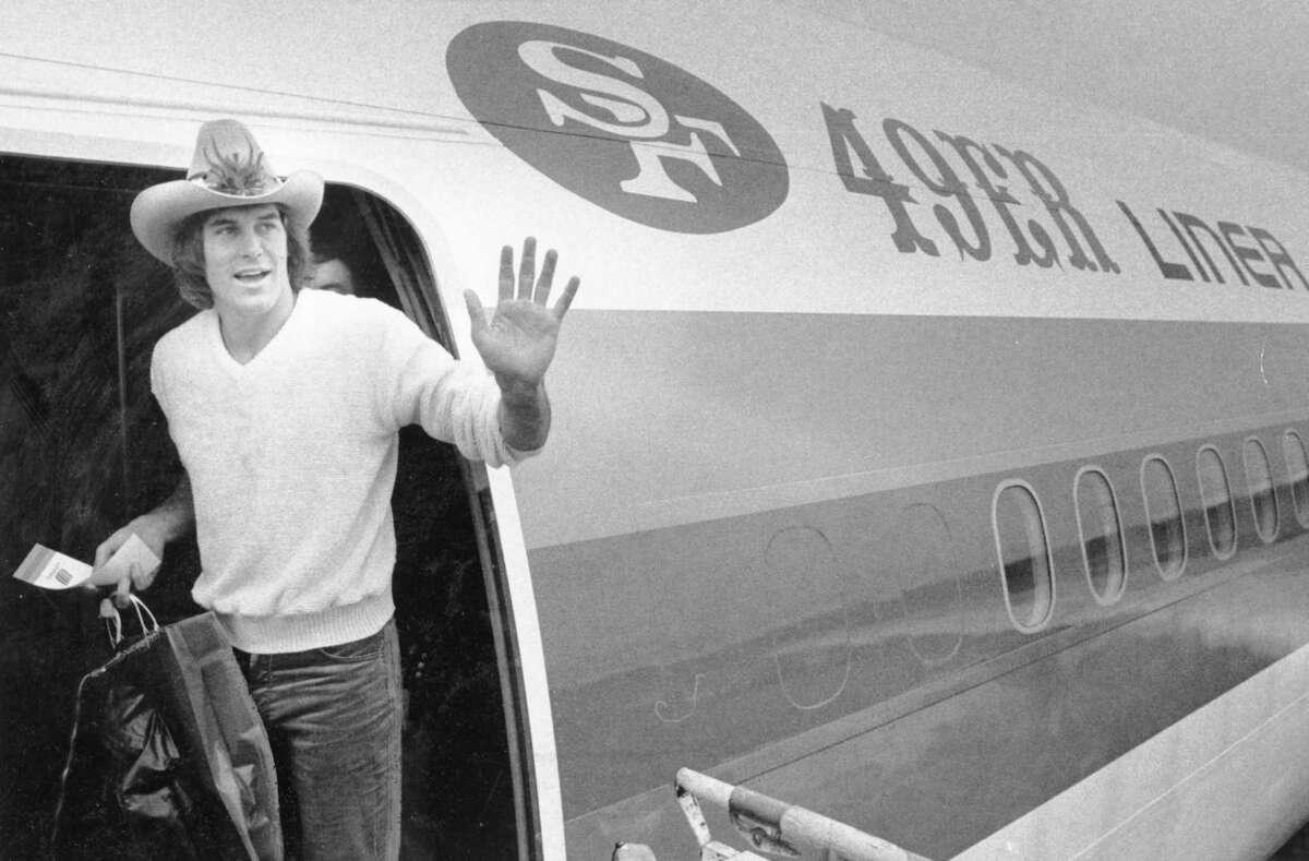 Dwight Clark climbs on a charter plane leaving for Pontiac. Jan, 18, 1982.