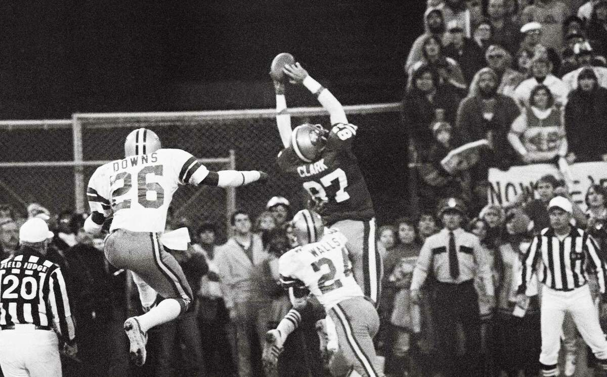 San Francisco 49ers Dwight Clark (87, WR), goes up in the air in the end zone for the game-tying touchdown pass from Qb Joe Montana to set up the PAT which beat the Dallas Cowboys to give the 49ers their first NFC Championship and Super Bowl berth. At right is Cowboys Michael Downs (26, S) and at right Everson Walls (24, CB).