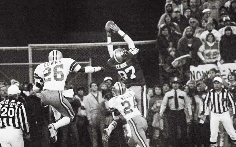 (Original Caption) San Francisco 49ers Dwight Clark (87, WR), goes up in the air in the end zone for the game-tying touchdown pass from Qb Joe Montana to set up the PAT which beat the Dallas Cowboys to give the 49ers their first NFC Championship and Super Bowl berth. At right is Cowboys Michael Downs (26, S) and at right Everson Walls (24, CB). Photo: Bettmann Archive / This content is subject to copyright.