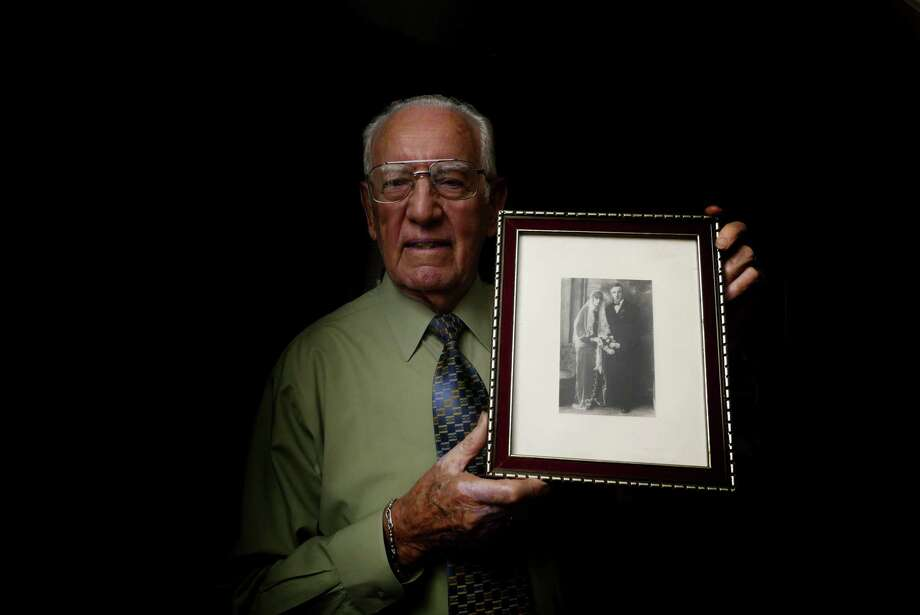 Peter Hoefl, who was 10 years old during World War II, was forced to join the Hitler Youth in Freising, Germany. He immigrated to the United States, where served in the Air Force. He holds a photo of his parents, Johann and Walburga Hoefl. Photo: Billy Calzada /San Antonio Express-News / San Antonio Express-News