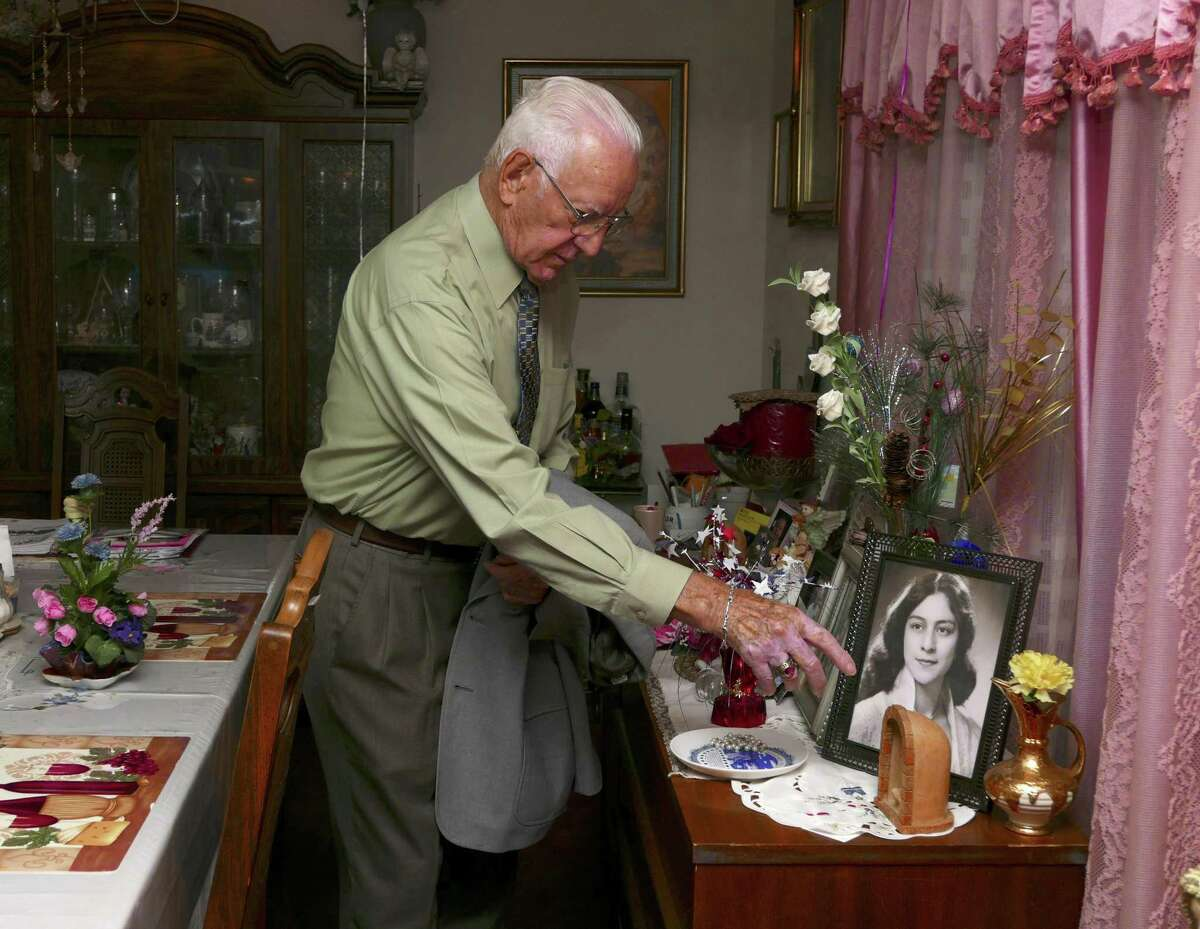 Peter Hoefl, 83, reaches for a portait of his wife, Angela, at their home. He was 10 years old during World War II, when he was forced to join the Hitler Youth in Freising, Germany. He immigrated to the United States, where he served in the Air Force.
