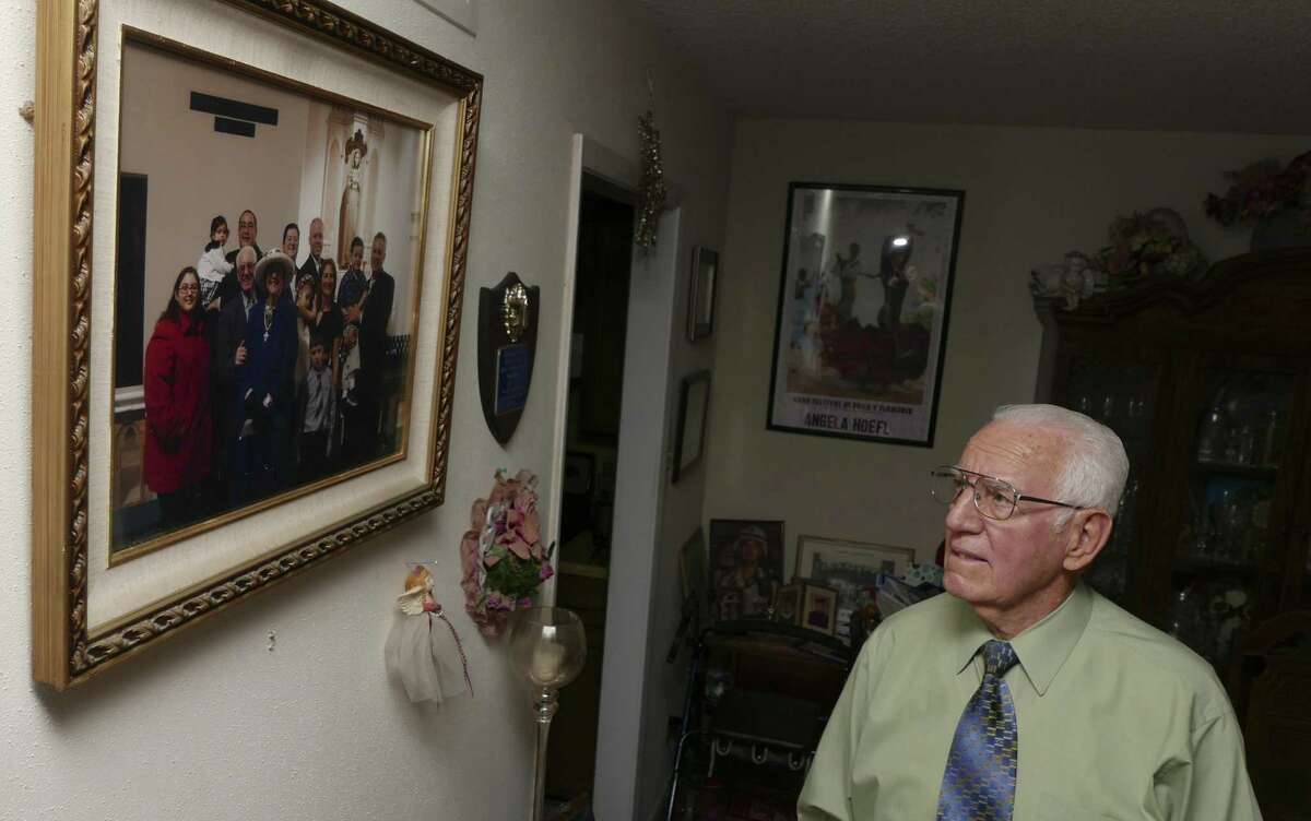 Peter Hoefl, looks at a portrait of his family. He was 10 years old during World War II and was forced to join the Hitler Youth in Freising, Germany. He immigrated to the United States, where served in the Air Force.