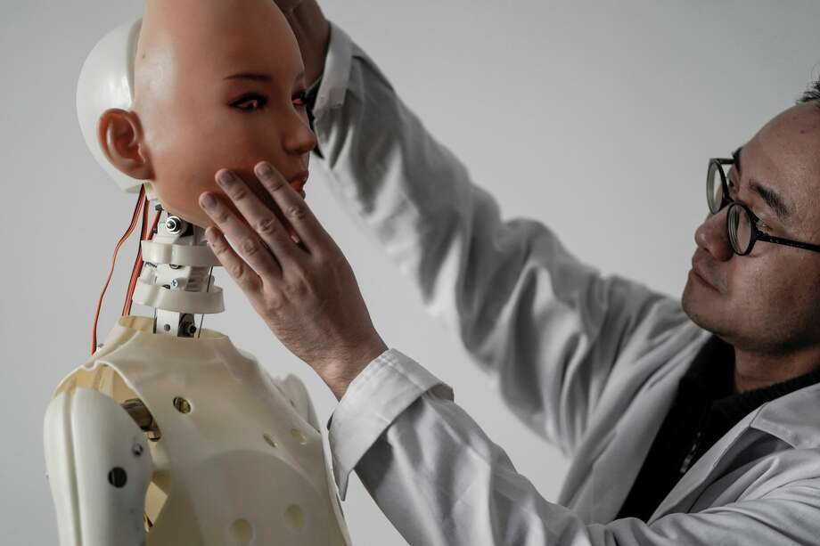 This photo taken on February 1, 2018 shows an engineer holding a silicon face against the head of a robot at a lab of a doll factory of EXDOLL, a firm based in the northeastern Chinese port city of Dalian. Photo: FRED DUFOUR/AFP/Getty Images