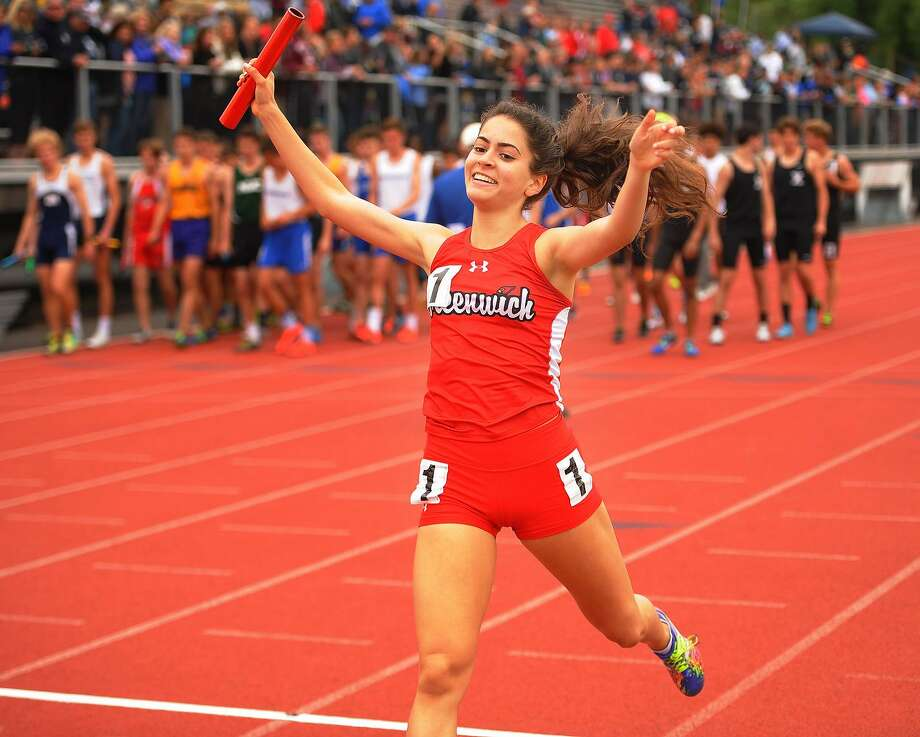 Greenwich's Emily Philippides raises her arms in victory as she crosses the finish line on the anchor leg of the girls 4x800 meter relay at the CIAC Track & Field Championships in New Britain on Monday. Photo: Brian A. Pounds / Hearst Connecticut Media / Connecticut Post