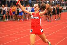 Greenwich's Emily Philippides raises her arms in victory as she crosses the finish line on the anchor leg of the girls 4x800 meter relay at the CIAC Track & Field Championships in New Britain on Monday.