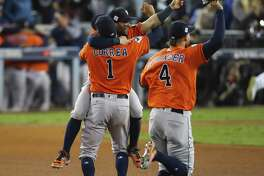 Houston Astros center fielder George Springer (4), second baseman Jose Altuve (27) and shortstop Carlos Correa (1) celebrate as the Astros beat the Dodgers 5-1 in Game 7 of the World Series at Dodger Stadium on Wednesday, Nov. 1, 2017, in Los Angeles. ( Michael Ciaglo / Houston Chronicle )