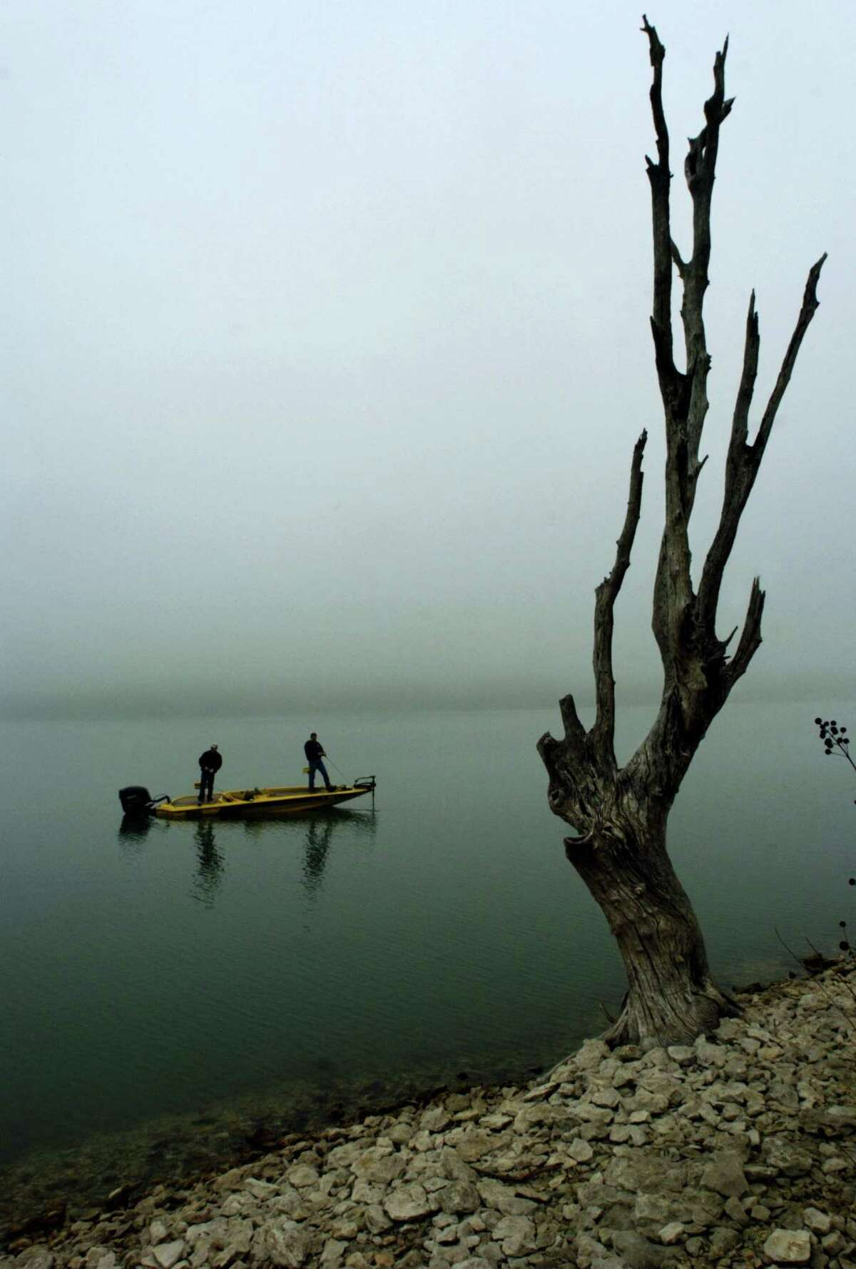 B.J. Gibson, left, and Travis Daugherty, of Jarrell, Texas, fish off their boat on Lake Belton as a recent wave of dense fog hits Central Texas and surrounds them Tuesday, Feb. 21, 2006, in Temple, Texas.