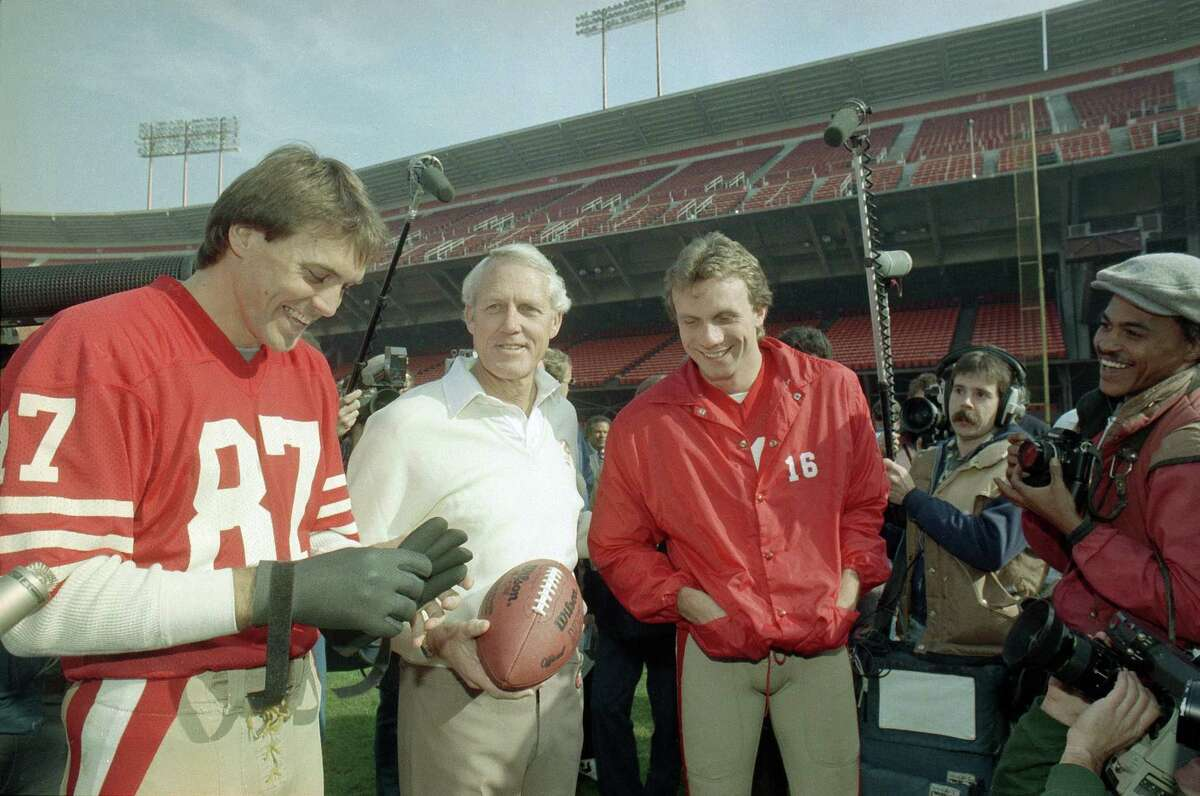 San Francisco 49ers' head coach Bill Walsh, center, shares a laugh with quarterback Joe Montana, in red jacket at right, and receiver Dwight Clark, left, during picture day at San Francisco's Candlestick Park, Jan. 16, 1985. The 49ers will meet the Miami Dolphins in Super Bowl XIX on Sunday.