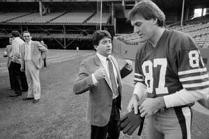 San Francisco 49ers wide receiver Dwight Clark (87) listens to a few words from 49ers owner Eddie De Bartolo Jr., before picture day in San Francisco, Jan. 16, 1985. Since De Bartolo bought the losing team seven years ago, it has won the division championship three times, won the Super Bowl once and is now going for a second Super Bowl victory.