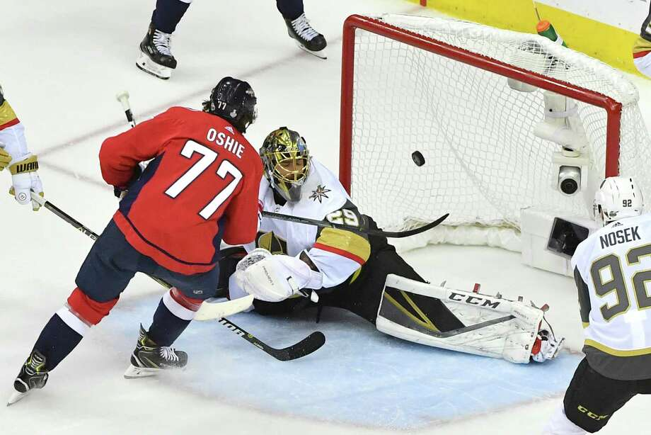 bc6119ef355 Washington Capitals right wing T.J. Oshie (77) scores around the defense of  Vegas Golden
