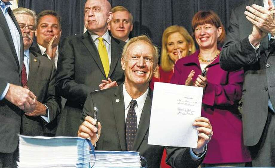 Gov. Bruce Rauner displays the signed state budget on Monday. It is the first full-year spending plan he's enacted since taking office in 2015. The Republican, who's seeking re-election in November, was joined at the bill signing by legislators from both parties, who hailed the budget as a bipartisan compromise. Photo:       Tyler LaRiviere | Sun Times (AP)