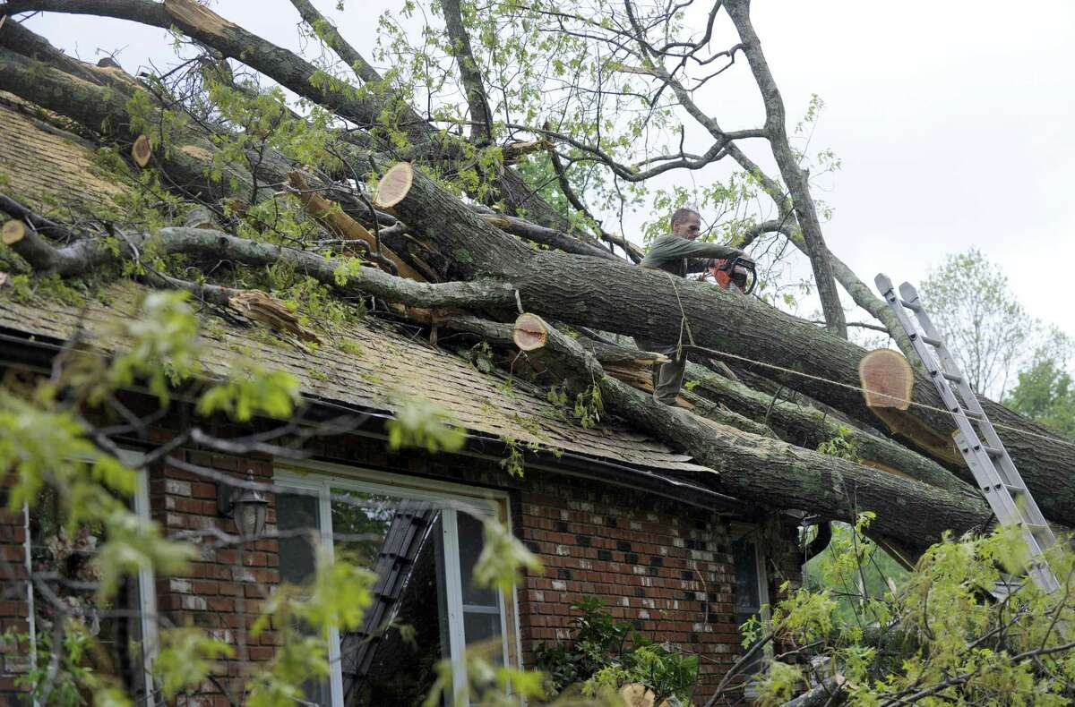 Shawn Brady of J & S Contracting in New Milford, cuts tree limbs off of a house on Elbow Hill in Brookfield Wednesday, May 16, 2018, a result of Tuesday's storm.
