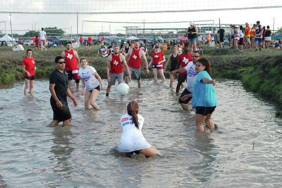 Lizzbeth Perez, shown making a hit for her team, was among the mud volleyball enthusiasts who showed up for at that event at this year's Pasadena Strawberry Festival. But festival attendance and sponsorships were down this year, with possible reasons including the Santa Fe shooting, an explosion at a Santa Fe plant and lingering effects of Hurricane Harvey, a fest spokeswoman says.