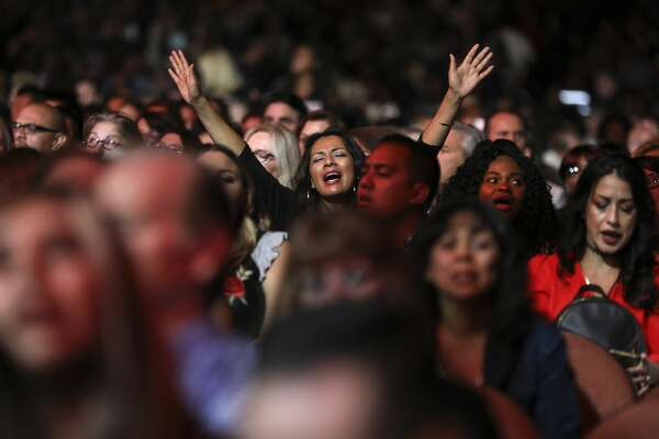 Attendees at a A Night of Hope event raised their arms in worship during a music-filled show. Ushers passed collection buckets. Joel recounted the growth of Lakewood Church and encouraged the crowd to stay rooted in hope.