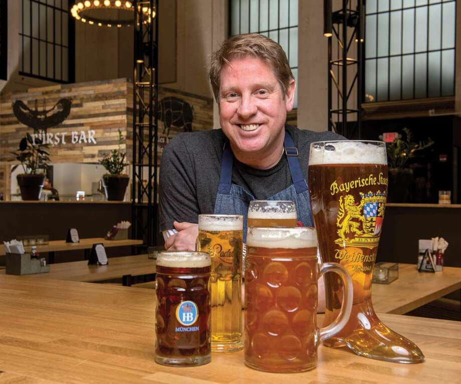Stephen Lewandowski, owner and chef of Harlan Haus in Bridgeport, with some of the beers he offers, including his own Harlan Honey Kolsch, center front. Do you dare get the 2-liter Das Boot? Photo: Mara Lavitt