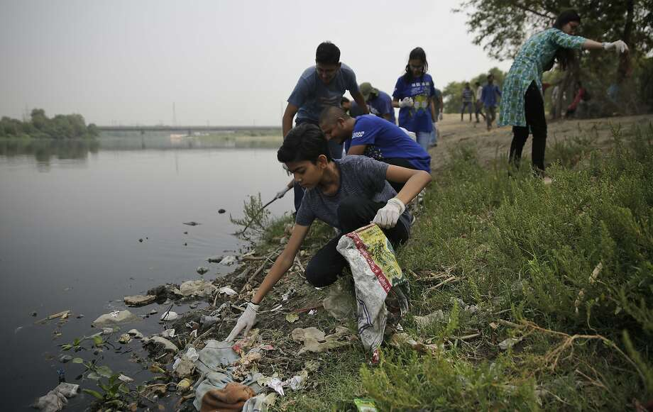 """Volunteers clean the banks of Yamuna, India's sacred river that flows through the capital of New Delhi. This year the theme of World Environment Day is """"Beat Plastic Pollution."""" Photo: Altaf Qadri / Associated Press"""