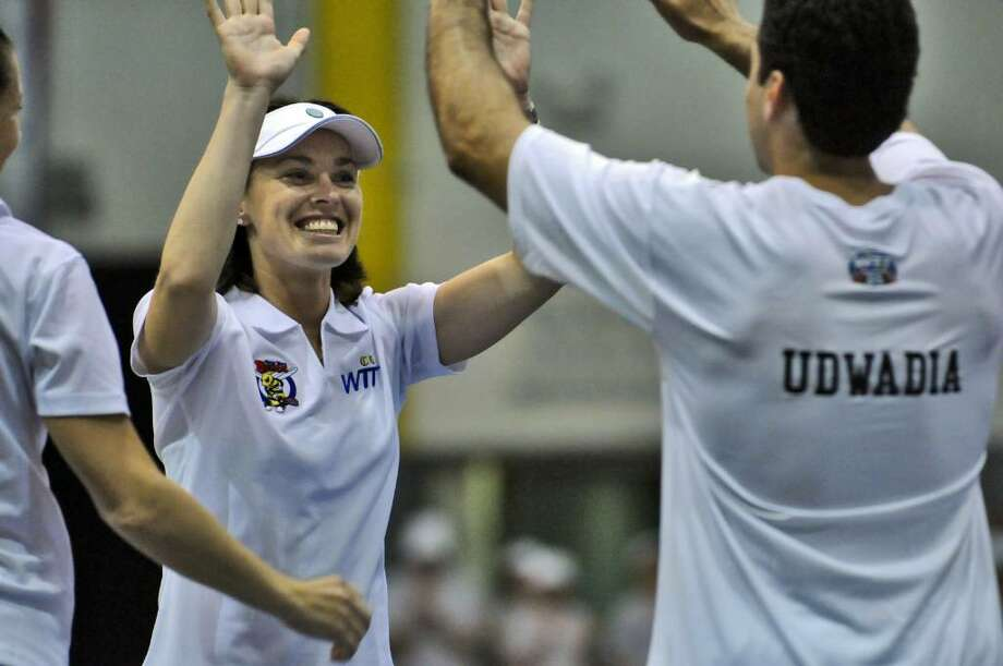 Martina Hingis, left, high-fives New York Buzz coach Jay Udwadia, right, during introductions before the start of their World TeamTennis match against the Philadelphia Freedoms on Monday night at SEFCU Arena at the University at Albany. The Buzz lost 21-20 in their season opener. (Philip Kamrass / Times Union ) Photo: PHILIP KAMRASS