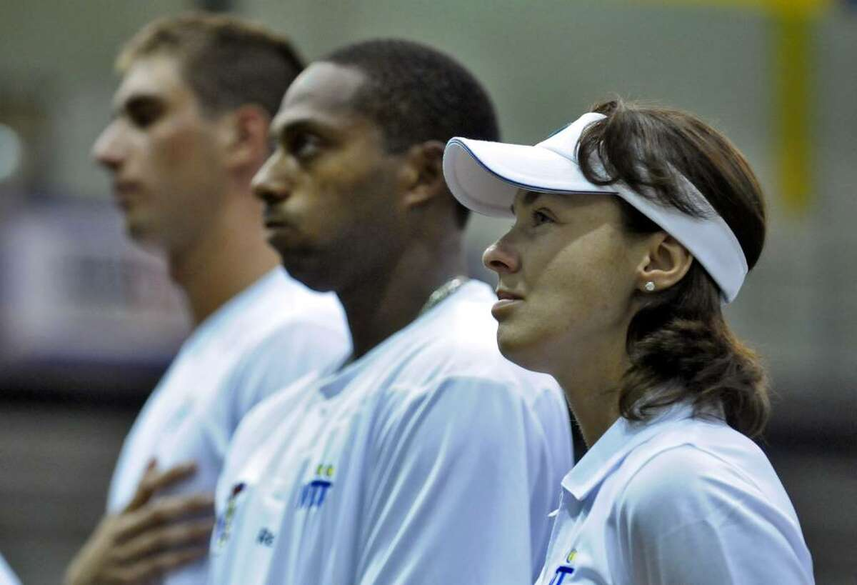 Martina Hingis, right, stands with New York Buzz teammates during the playing of the national anthem before the start of their World TeamTennis match against the Philadelphia Freedoms on Monday night at SEFCU Arena at the University at Albany. Joining her are teammates Alex Domijan, left, and Scoville Jenkins. The Buzz lost their season opener, 21-20. (Philip Kamrass / Times Union )