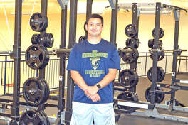 Father McGivney athletic director Jeff Oller poses in the school's weight room, which opened last summer. FMCHS continues to add to the number of sports it offers.