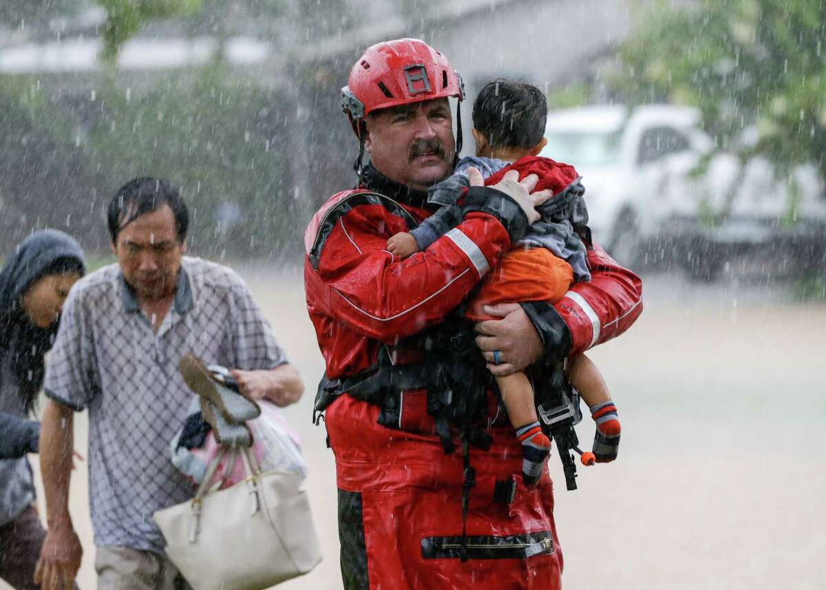 Chad Smith, a Task Force One member from the Dallas Fire Department, carries 1-year-old Christian Rodriguez from a rescue boat as people are transferred to a pickup point along Edgebrook in Houston on Sunday, August 27, 2017, after Hurricane Harvey inundated the area.
