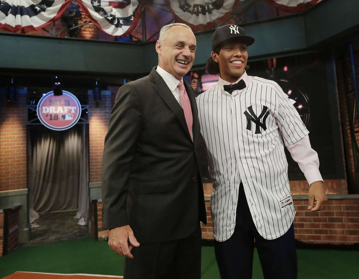 Anthony Seigler, right, a catcher from Cartersville High School in Georgia, poses for photos with Baseball commissioner Rob Manfred after being selected 23rd by the New York Yankees during the first round of the Major League Baseball draft Monday, June 4, 2018, in Secaucus, N.J. (AP Photo/Frank Franklin II)