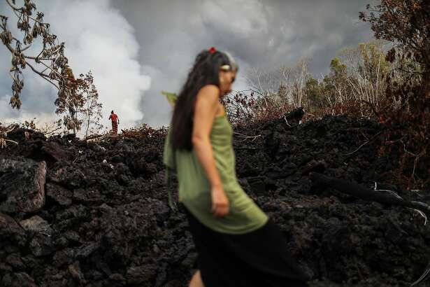 PAHOA, HI - MAY 27:  A traditional hula practitioner (C) carries an offering while walking on a cooled recent lava flow from a Kilauea volcano fissure, on Hawaii's Big Island, on May 27, 2018 in Pahoa, Hawaii. Offerings were left in a ceremony for Madame Pele, the Hawaiian goddess of volcanoes and fire. Hula is a Hawaiian dance form accompanied by chants or songs which trace the history and culture of Hawaii. The Big Island, one of eight main islands that make up Hawaii state, is struggling with tourist bookings following the Kilauea volcano eruptions, with summer bookings at the island down 50 percent. Officials stress that the eruptions have thus far only affected a small portion of the island.  (Photo by Mario Tama/Getty Images)