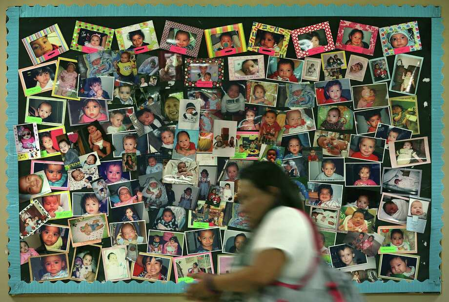 A mother passes a bulletin board with photos of babies born to addicted mothers, at the Center for Health Care Services, on Thursday, Sept. 7, 2017. Mothers attend Mommies Class at the center. Photo: Bob Owen, Staff / San Antonio Express-News / ©2017 San Antonio Express-News