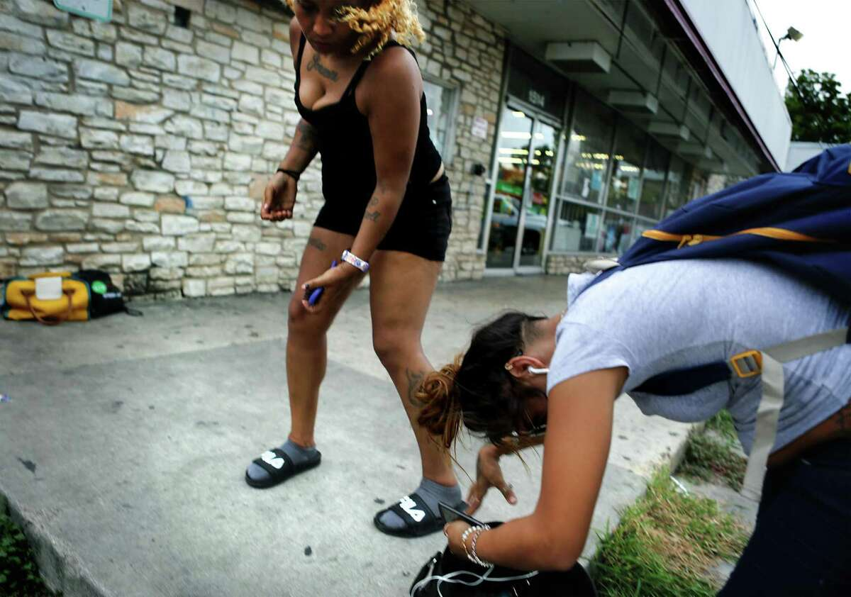 Two unidentified women, both heroin addicts, exchange words in front of a strip mall on S. New Braunfels, where Sean Baker an Outreach worker with Center for Health Care Services, was handing out personal care bags, water, snacks, and condoms to addicts he finds, on Monday, Sept. 25, 2017.