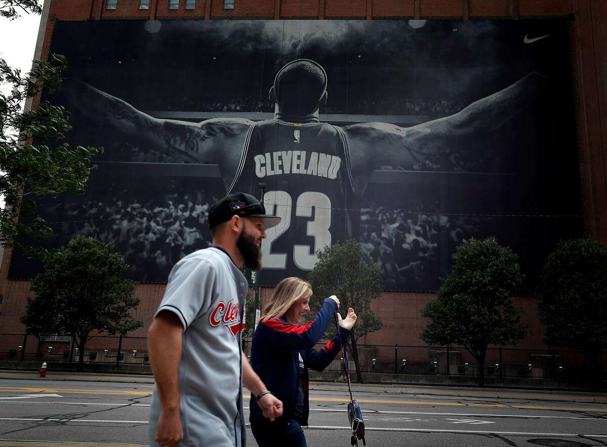 Tiffany and Nathan Fulk walk in front of the LeBron James banner hanging near the Quicken Loans Arena in their Cleveland Indians attire the day before the Golden State Warriors play the Cleveland Cavaliers in Game 3 of the NBA Finals in Cleveland, Ohio, on Tuesday, June 5, 2018.