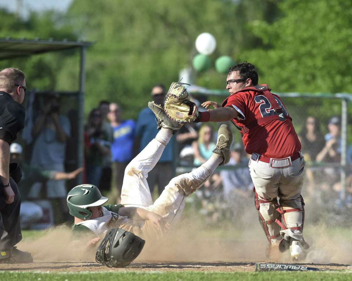 Green wich catcher Cristian Perez (23) tags out New Milford's JonLuc Dumas for the final out of their Class LL state playoff game Tuesday at New Milford High School.