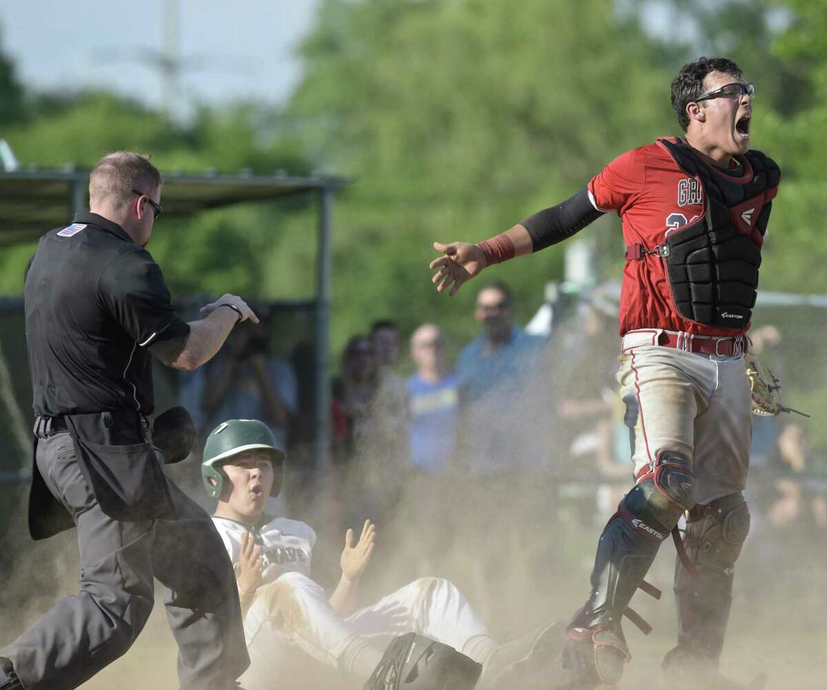 Greenwich catcher Cristian Perez celebrates after tagging out New Milford's JonLuc Dumas for the final out Tuesday in Greenwich.