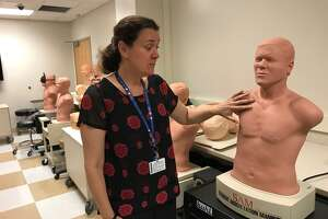 Dr. Mara McErlean, director of Albany Medical College's Patient Safety and Clinical Competency Center, in a room of training manikins. (Paul Grondahl / Times Union)