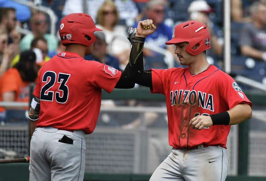 Arizona's Zach Gibbons (23) celebrates with teammate Cesar Salazar, right, after Salazar scored against Oklahoma State in the second inning of an NCAA men's College World Series baseball game, Friday, June 24, 2016, in Omaha, Neb. (AP Photo/Ted Kirk) Photo: Ted Kirk, FRE / Associated Press / AP2016