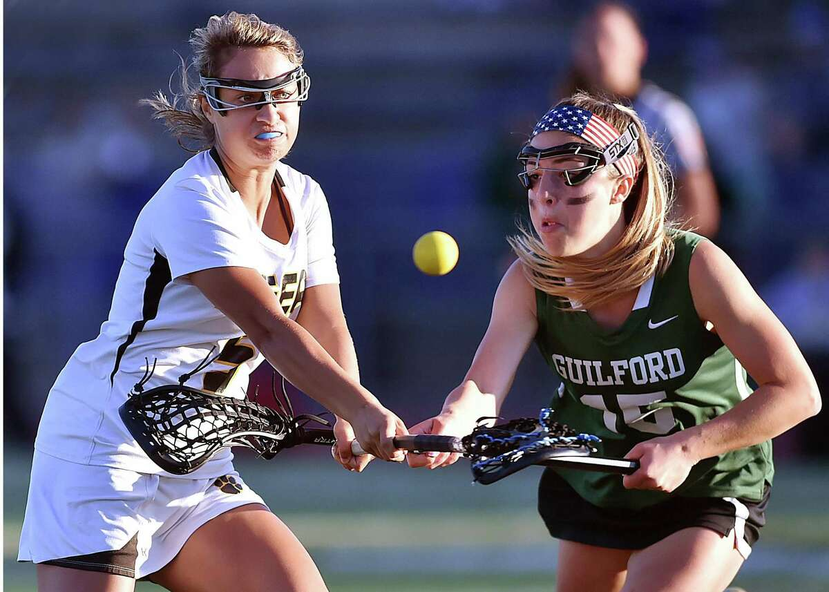 Hand's Taylor Scully fires a shot and scores as Guilford's Hannah McDermott defends on Tuesday.