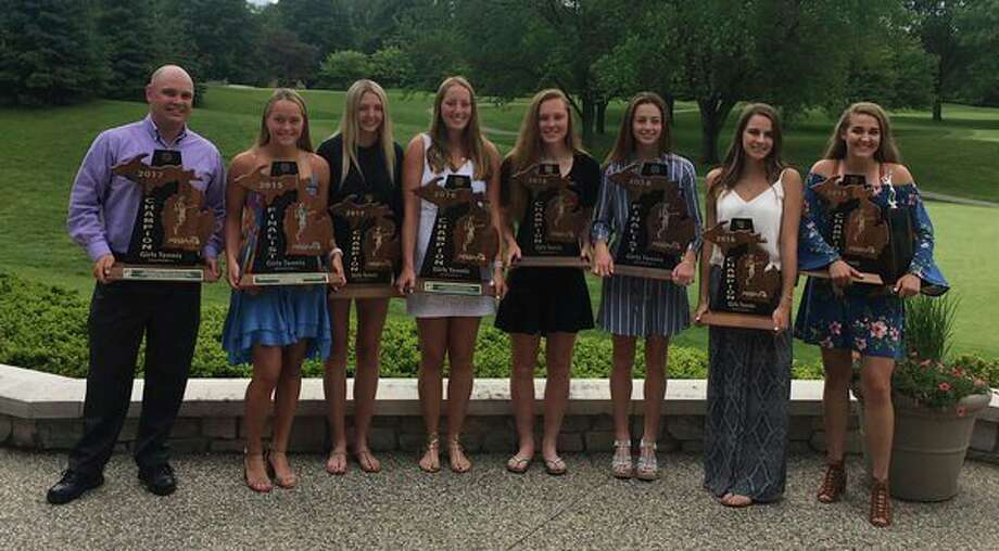From left, Dow girls tennis coach Garrett Turner and senior tennis players Tatum Mathews, Christina VanderKelen, Hadley Camp, Sarah Ismail, Giacomina Fabiano, Jessica Brown and Kelly Livingston hold all the trophies of which the senior class has been a part over the last four years. The seven seniors helped the program win two team state titles, two second-place finishes, four regional titles and 10 individual state titles in singles and doubles. (Photo provided)