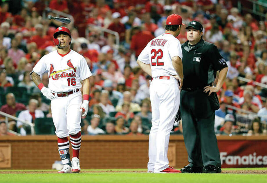 The Cardinals' Kolten Wong, left, flips his bat as he walks away after being called out by home plate umpire Doug Eddings, right, on batter interference, as Cardinals manager Mike Matheny pleads Wong's case in the sixth inning of Tuesday night's game against the Miami Marlins in St. Louis. Photo:       Jeff Roberson | AP Photo